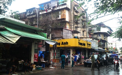 Police surround a Hanoi tenement in an effort to rescue the last hostage of the three that were held Tuesday morning. Photo: Ha An