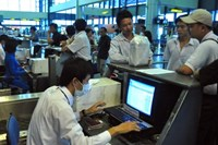 File photo shows an airport officer conducting check-in procedure for passengers in Hanoi, Vietnam.