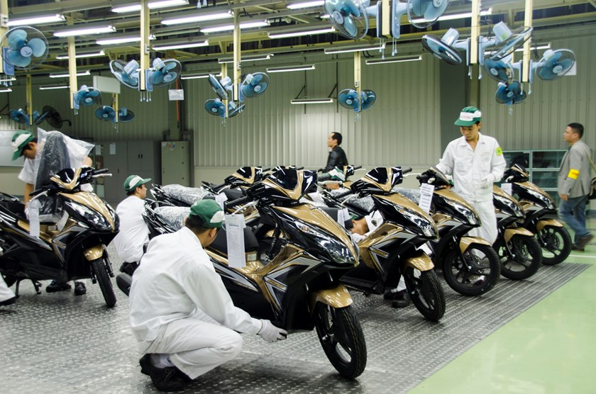 Workers check the quality of newly assembled scooters at a new Honda motorcycle plant in Vietnam. Photo: Thang Tran