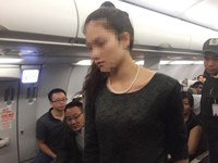 One of the two women being escorted off the plane by a member of the airport's security team. File photo.