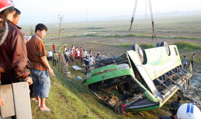 A bus is seen turn over on a paddy field in Nghe An province on Friday morning. The accident has killed 1 and injured 19 others. Photo: VD