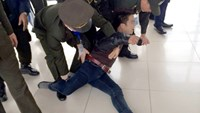 Security guards at Noi Bai airport seize a man following a bizarre outburst at the check-in counter on Monday morning.