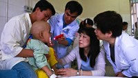Kazuyo Watanabe (2nd from R) taking care of a little patient with cancer in the Hue Central Hospital. Photo: N.Hien