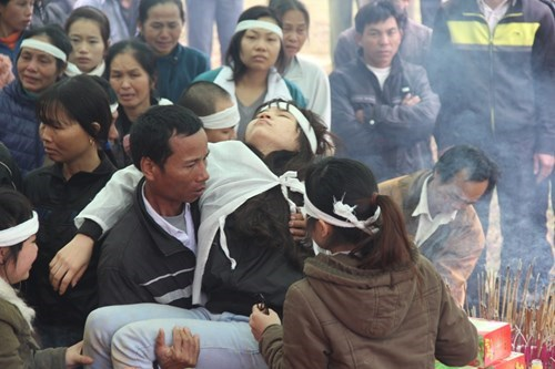 A woman faints at the funeral of a victim, who was killed in the collision. Photo: Phan Ngoc