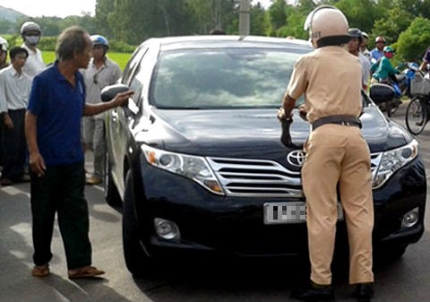 A police officer and some locals stop the car of Dinh Thi Huong Thuy. Photo credit: Tien Phong