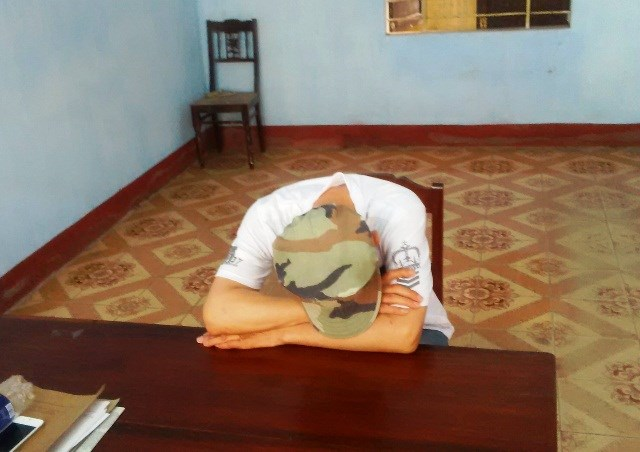 "Ha Cuong, 49, sleeping in a police station in Hue Saturday. He had beendrinking at a local bar when he allegedly stabbed another bargoer to death forgazing at him ""vulgarly"". Photo courtesy of the police."