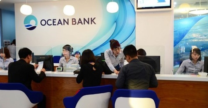File photo shows customers doing business transactions at the Ocean bank in Hanoi.