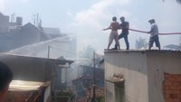 Firefighters stands on the roof of a house, trying to stop a blaze spreading from nearby houses in Ho Chi Minh CIty. Photos: Duc TIen