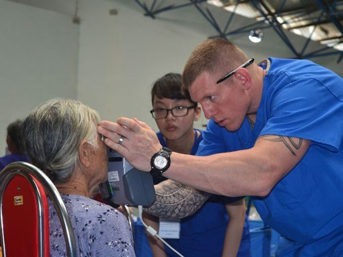 A PACANGEL volunteer performs an eye check on an elderly woman in Quang Ngai. Photo: Hien Cu