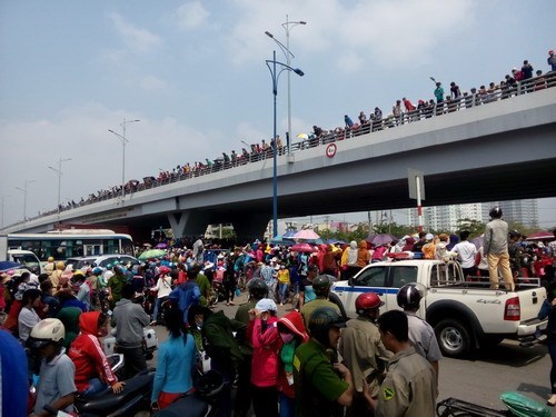 Thousands of workers pouring into the road, climbing on an overpass in Tan Tao Industrial Zone, Ho Chi Minh City, during a wildcat strike to demand for the right to severance pay. Photo: Trung Hieu