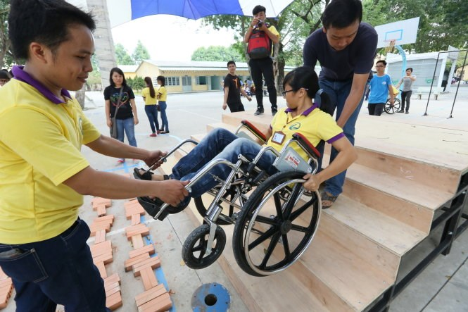 Volunteers practice to support a wheelchair user at a training course in Ho Chi Minh City last November. File photo.