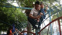 A man tries to carry his daughter over a fence to get into a water park in Hanoi for free. Photo credit: Thanh Nien, Vnexpress