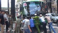 A dozen locals trying to push and lift the front part of a bus on, rescuing two riders scrolled into the bus ground. Photo credit: Tuoi Tre