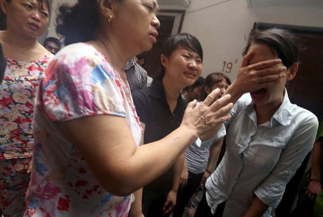 Neighbors and relatives mourn for five people killed in a blaze in Hanoi last night. Photo credit: VnExpress