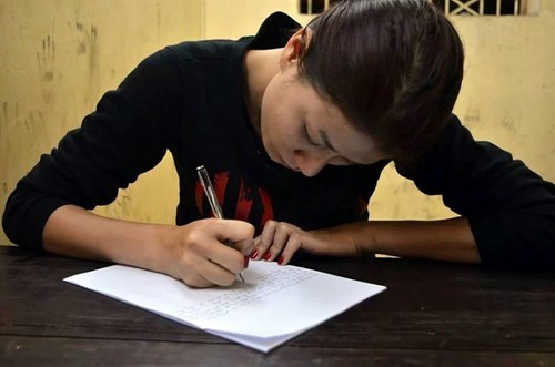 Tran Thi Trang signs her statement at the police station on February 28