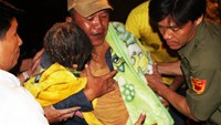 A rescuer carries Tu Anh, 7, in his arms. Photo: Do Truong