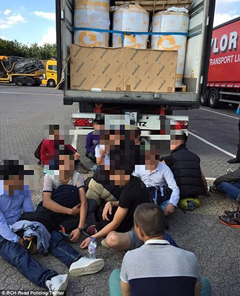 The group of 18 migrants were found by police on the M1 motorway north of London. Photo credit: Express