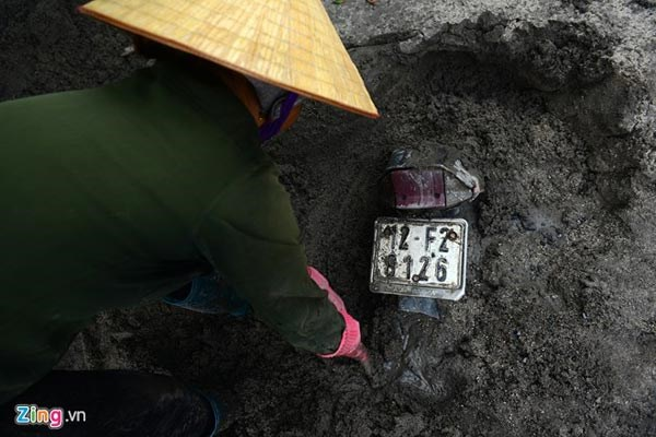A woman tries to remove a motorbike buried under a thick, solidified layer of mud. Photo credit: Zing