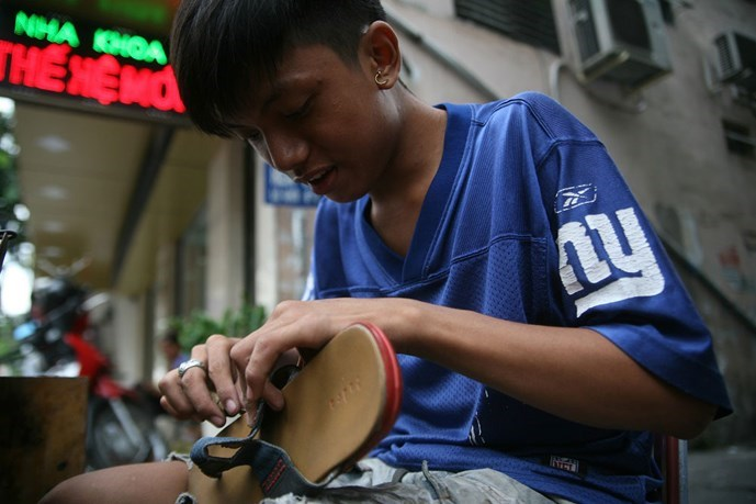 Nguyen Quoc Cuong repairs a pair of flip-flops at his tiny stall in Ho Chi Minh City. Photos: Tran Khang