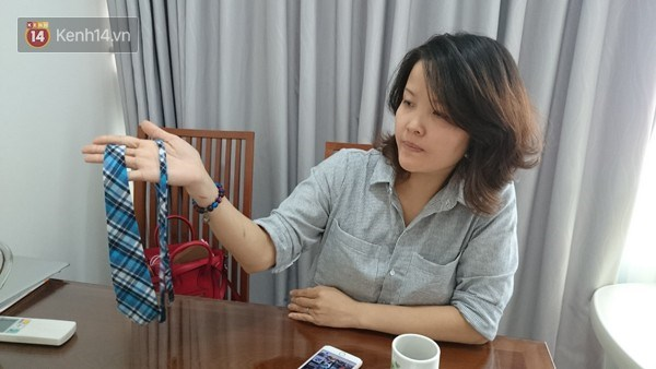 Nguyen Thanh Hieu shows a tie that is part of her son's school uniform. Photo credit: Kenh14