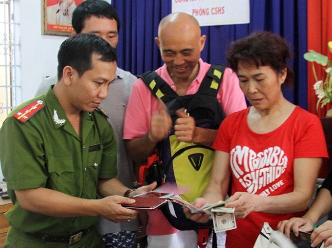 Chinese tourist Wang Fan, 61, receives her belongings from local police in Nha Trang. Photo credit: Tuoi Tre.