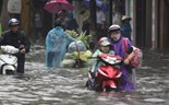 A woman walks her motorbike to take her child to school on a flooded street in Hai Phong on Monday morning. Photo: Luu Quang Pho