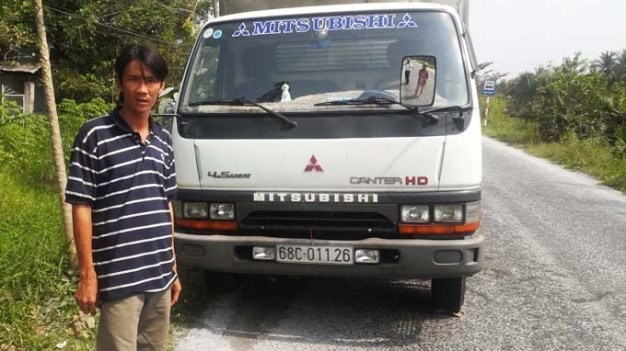 Driver Luong Hoang My poses in front of the truck after winning a case against local police on September 8, 2015. Photo credit: Tuoi Tre.