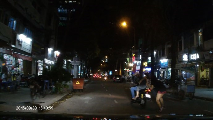 A still photo taken from a dash  cam video in which two snatchers trying to grab a handbag from a passer-by in Ho Chi Minh City.
