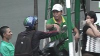 A still from a video captured by Thanh Nien shows an employee (wearing white hat) of the Tran Thien filling station arguing with a customer after the customer discovered his trick.