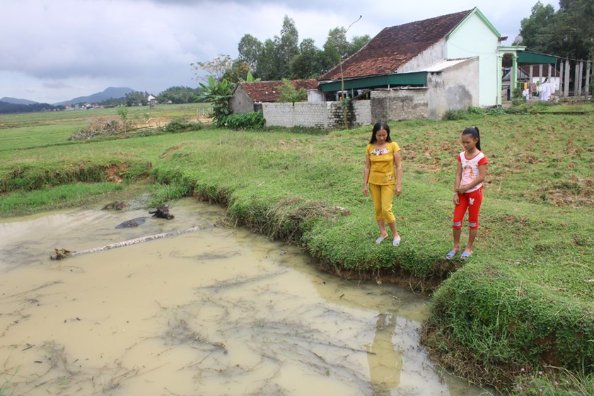 Nguyen Thi Van Anh (R) stands near a deep pond where she saved two little boys on October 31. Photo: Hoang Lam/Dan Tri