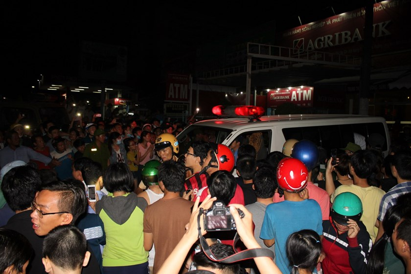 Hundreds gather around an ambulance which carries Phan Van Tuan to the hospital on Tuesday evening. Photo: Le Lam