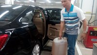 A driver with a can of A95 gasoline drained out from his damaged car. Photo: Hieu Trung