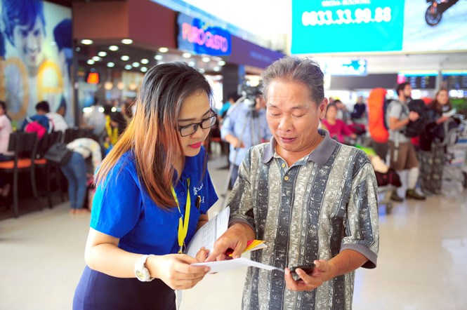 A volunteer assists a passenger to check in at tan Son Nhat International Airport in ho Chi Minh City on February 3, 2016. Photo: Le Thanh