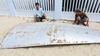 Two fishermen in Khanh Hoa Province pose with a metal sheet they have fished out from the sea. Photo: Ngoc Minh
