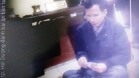 A still photo from a one-minute video shows Lieutenant-colonel Pham Thanh Giang (R) playing cards with three others inside his office
