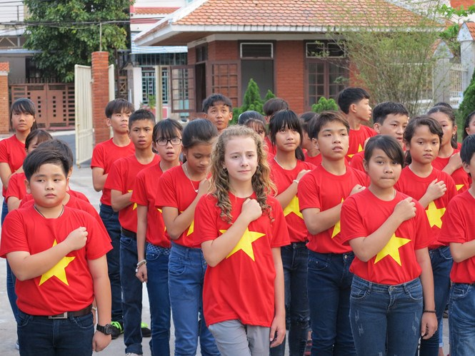 Capri Everitt, 11, sings Vietnam's national anthem with local children at the SOS village in Da Nang City in March. Photo: Dieu Hien