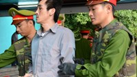 Do Thanh Son is escorted by police officers to a courtroom in Kien Giang Province on Thursday. Photo credit: Tuoi Tre