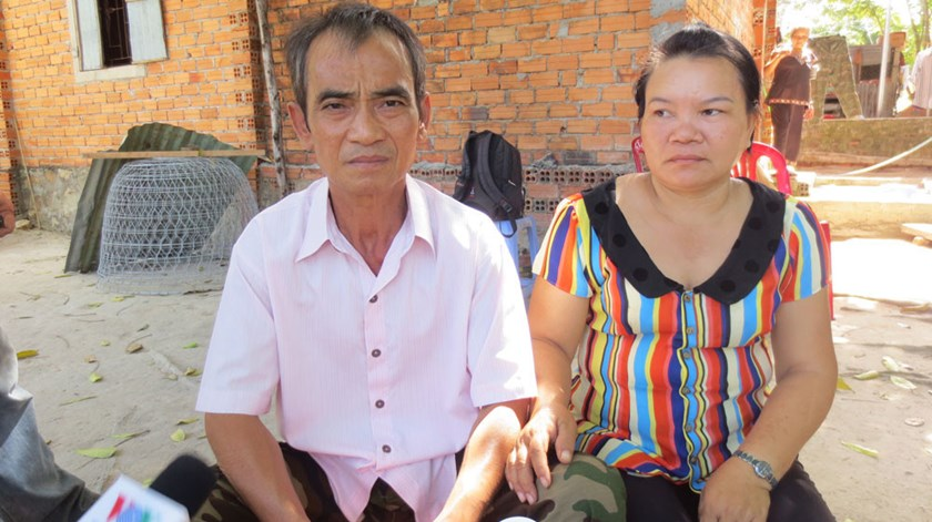 Huynh Van Nen sits beside his wife in front of their house in Binh Thuan Province. Photo: Que Ha