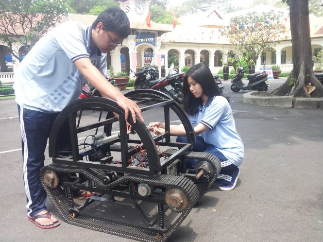 Pham Thanh Truc (L) and Nguyen Hoang Ngan next to their invention, the TN98 wheelchair. Photo credit: Tuoi Tre