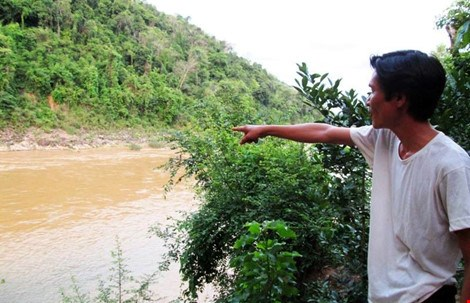 A man points to a river in Nghe An Province where a 6-year-old boy drowns on May 23, 2016. Photo credit: Lao Dong