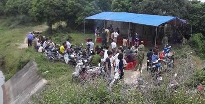 Locals gather near a dam in the northern province of Hai Duong where a 10-year-old boy has been found dead. Photo: CTV
