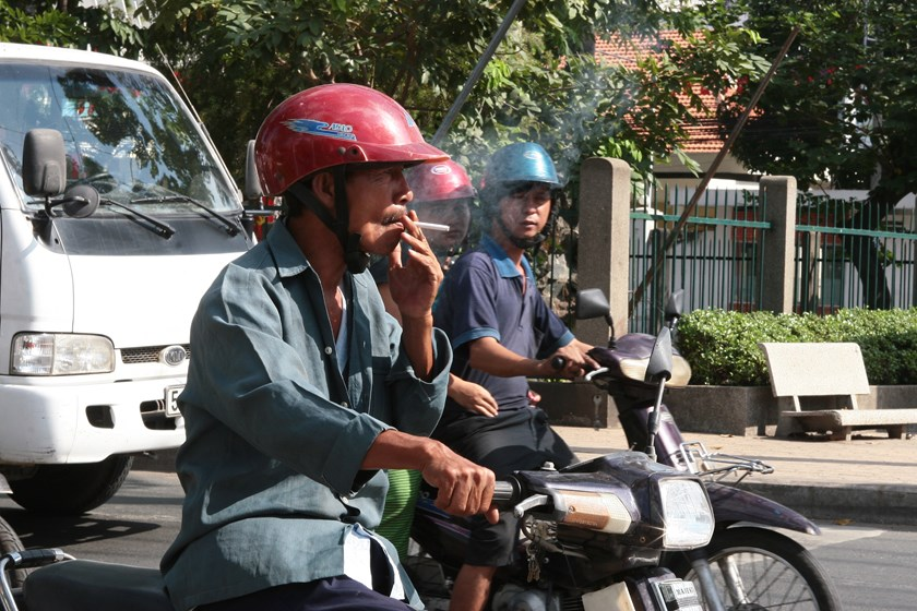 A man smokes while waiting for a red light on a street in Ho Chi Minh City.