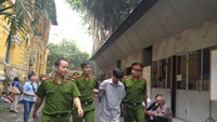 Kha Cu being escorted to the crime scene during investigation of his murder. Photo: Le Quang