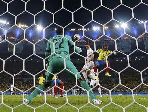 France's Olivier Giroud (2, R) jumps for the ball with Ecuador's Gabriel Achilier as he tries to score past goalkeeper Alexander Dominguez during their 2014 World Cup Group E soccer match at the Maracana stadium in Rio de Janeiro June 25. Photo credit:Reu