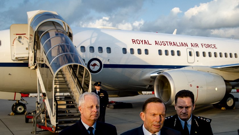 Australian Prime Minister Tony Abbott (C) answers journalists' questions upon his arrival at the Rotterdam The Hague Airport in Rotterdam, on August 10. Photo credit: AFP