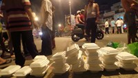 Boxes of rice on the pavement near the scene where Tran Minh Phuoc was stabbed to death when he was distributing free meals to poor people. Photo: Cong Nguyen