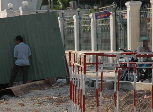 A man relieves himself on a construction fence in Ho Chi Minh City. Photo: Diep Duc Minh