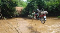A man pulls his motorbike across the Ea Rech Stream in Dak Lak Province on a cable. Photo: Ngoc Quyen