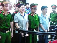 Duong Tu Trong (3, L) stands trial for helping his corrupt brother flee Vietnam. Photo: Ha An