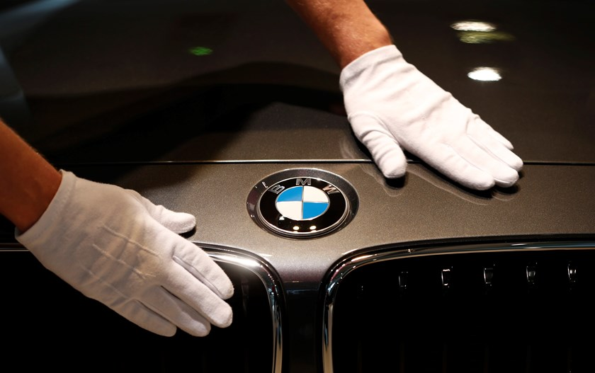 A man cleans a BMW logo on a car before the annual BMW press conference in Munich on March 19. Photo: Reuters
